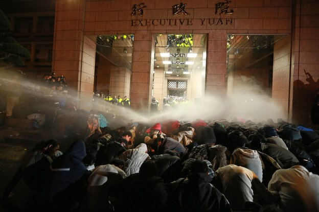 Police spray protesters with a water cannon during a demonstration outside the Executive Yuan in Taipei early Monday, following Taiwan President Ma Ying-jeou's refusal to scrap a contentious trade agreement with China.