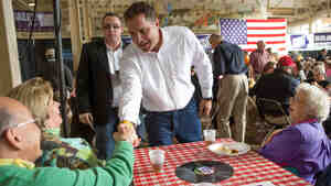 U.S. Senate candidate Bruce Braley talks to supporters Karen and Dennis Swallow during a barbecue lunch in October 2013 at the Iowa State Fairgrounds in Des Moines, Iowa.