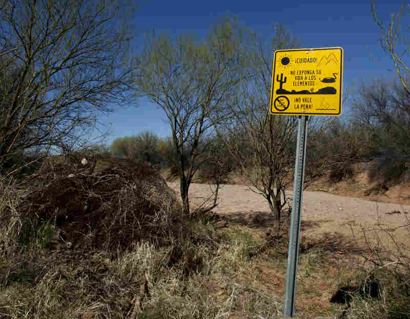 """A sign warns against the many dangers in the desert in Spanish, saying, """"It's not worth it."""""""