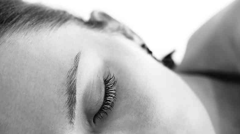 Close-up of a part of the face of young woman taking nap.