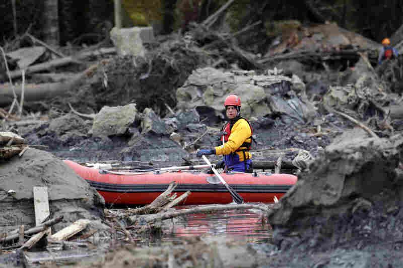 A searcher uses a small boat to look through debris in Oso. The Seattle Times reports that geological studies have warned for decades that the area of Snohomish County where Oso is located was at risk for landslides.