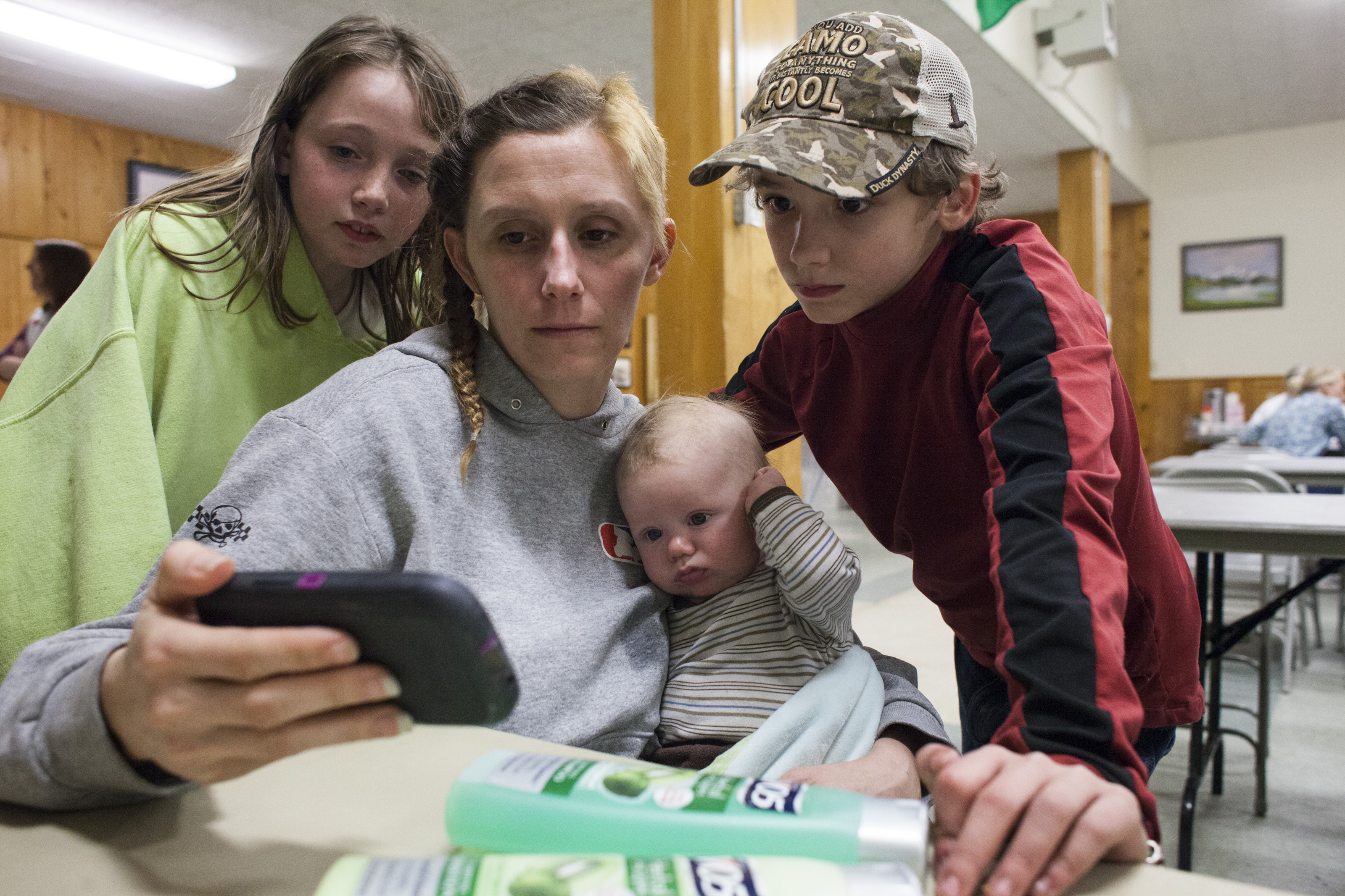 Trista Bonus (left) watches a news clip about the nearby mudslide with LoAnna Langton and her sons at a temporary Red Cross shelter in Darrington on Sunday. The Langton home was flooded by waters from the Stillaguamish River, which was partially blocked by the mudslide.