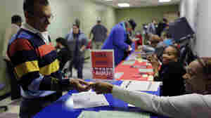 An election official checks a voter's photo identification at an early-voting polling site in Austin, Texas.