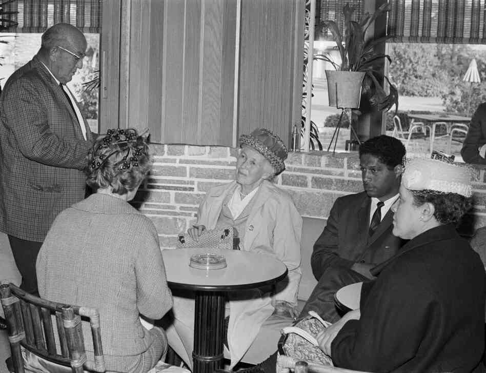 Sheriff L.O. Davis reads a set of local laws to Mrs. Malcolm Peabody, Dr. Robert Hayling and Mrs. John M. Burgess. The protesters remained seated as they attempted to integrate the dining room at a table in the Ponce De Leon Motor Lodge.