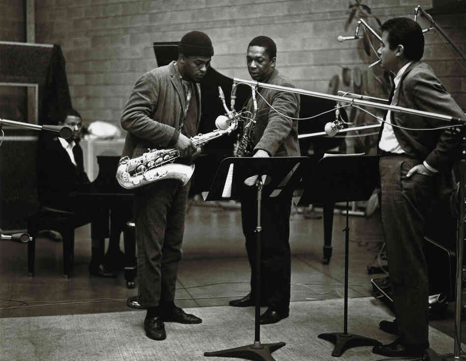"Coltrane (center right) discusses a passage of A Love Supreme with producer Bob Thiele (right), saxophonist Archie Shepp (center left) and pianist McCoy Tyner. Shepp played on the alternate take of the first movement, ""Acknowledgement."""