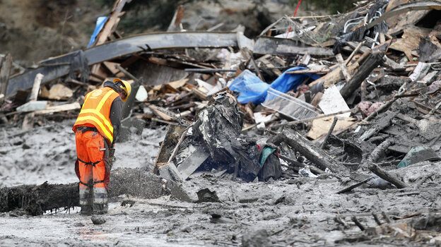 A worker uses a chain saw at the scene of the deadly mudslide near Oso, Wash.