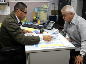Isaias Hernandez (left) counsels Paul Garcia on his finances at the Mexican American Opportunity Foundation in Montebello, Calif.