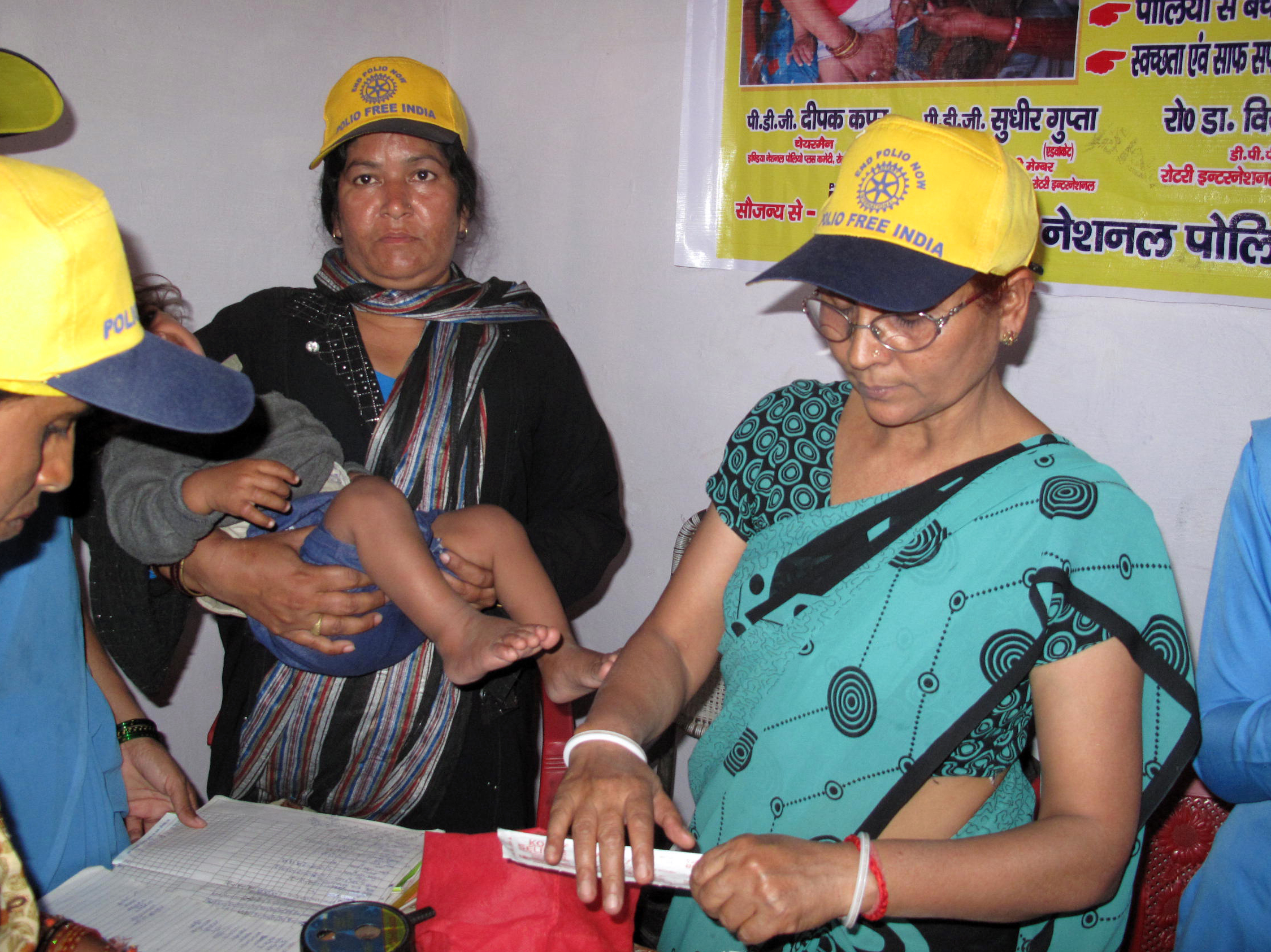 Polio vaccine campaigns are no longer just for fighting polio: Here health workers give a baby a shot against the measles in Moradabad, India.