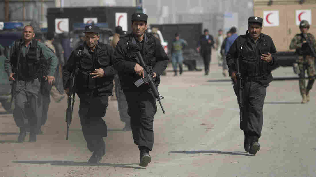 Afghan special forces rush to the scene as Taliban militants attack the main Afghan election commission's headquarters on the outskirts of Kabul, Afghanistan on Saturday.