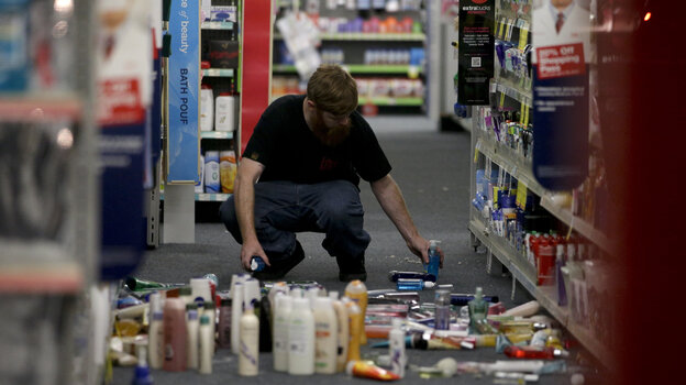 A man picks up fallen goods at a CVS store after an earthquake hit Friday near La Mirada, Calif. The magnitude-5.1 earthquake was widely felt in the