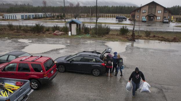 Volunteers unload donated supplies during heavy rains in