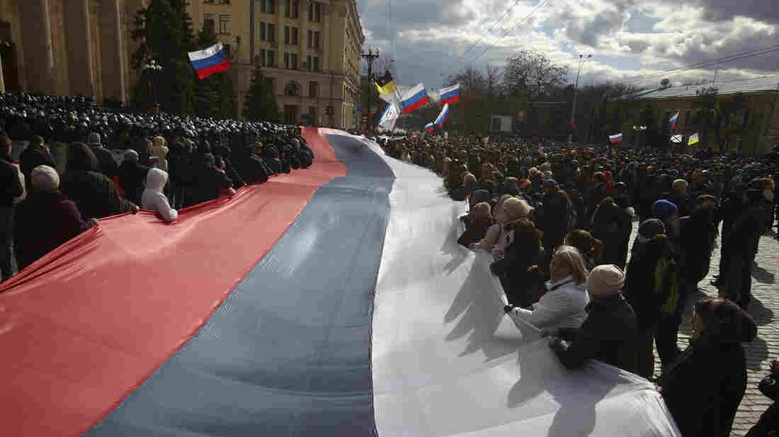 Demonstrators carry a giant Russian flag through Kharkiv, Ukraine, earlier this month. The city's population is a blend of  Ukranians and Russians, many of whom share families across the Russian border.