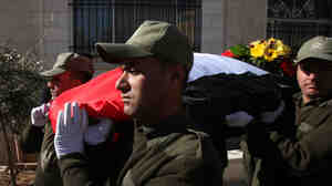 Jan. 8: Palestinian security guards carry the flag-covered body of Jamal al-Jamal, ambassador to the Czech Republic, during his funeral in the West Bank city of Ramallah.