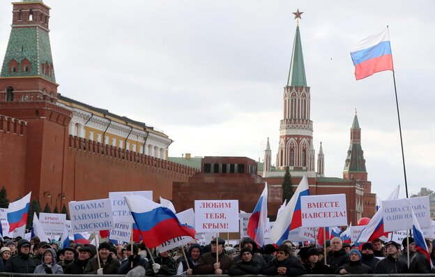 """Russians in Moscow's Red Square hold banners reading, """"Love You Crimea!"""" """"Together For All Time"""" and """"Obama, Think About Alaska!"""" during a March 18 rally celebrating the annexation of Crimea."""