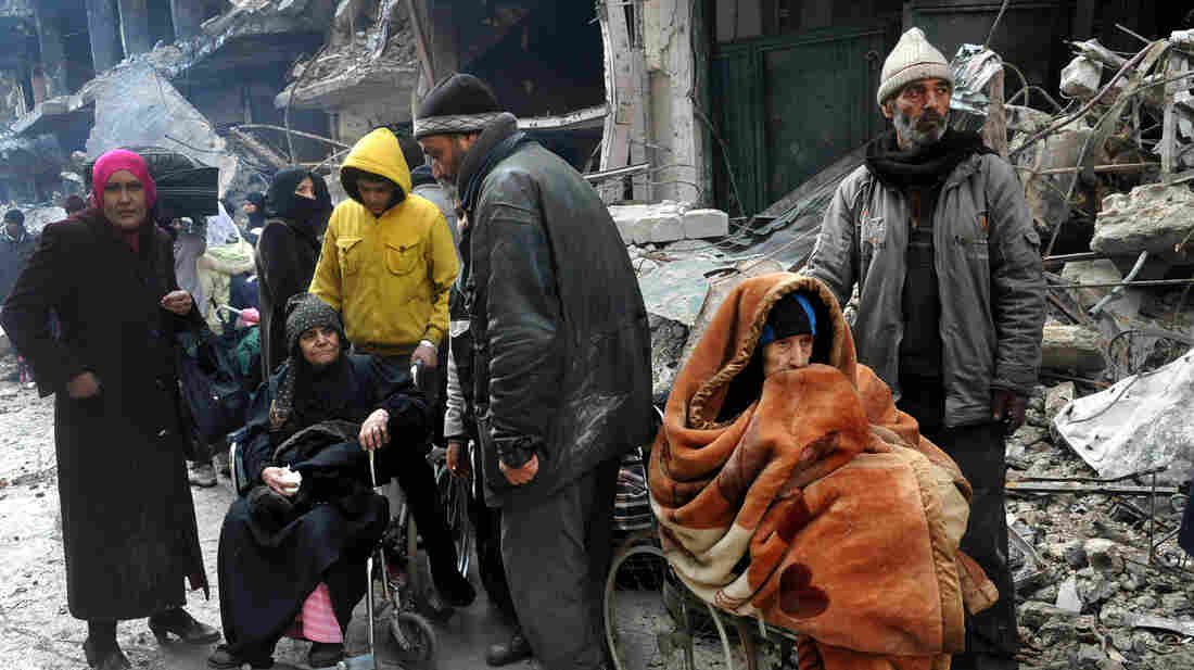 Palestinian residents of the besieged Yarmouk refugee camp wait to receive aid supplies from the United Nations on the southern edge of Damascus, Syria, on Feb. 4.