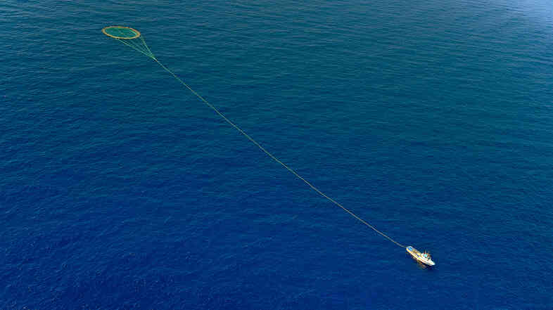 "A tuna fishing boat drags a cage of nets on the Mediterranean sea in 2010. (The Mediterranean is not considered to be part of the ""high seas."")"