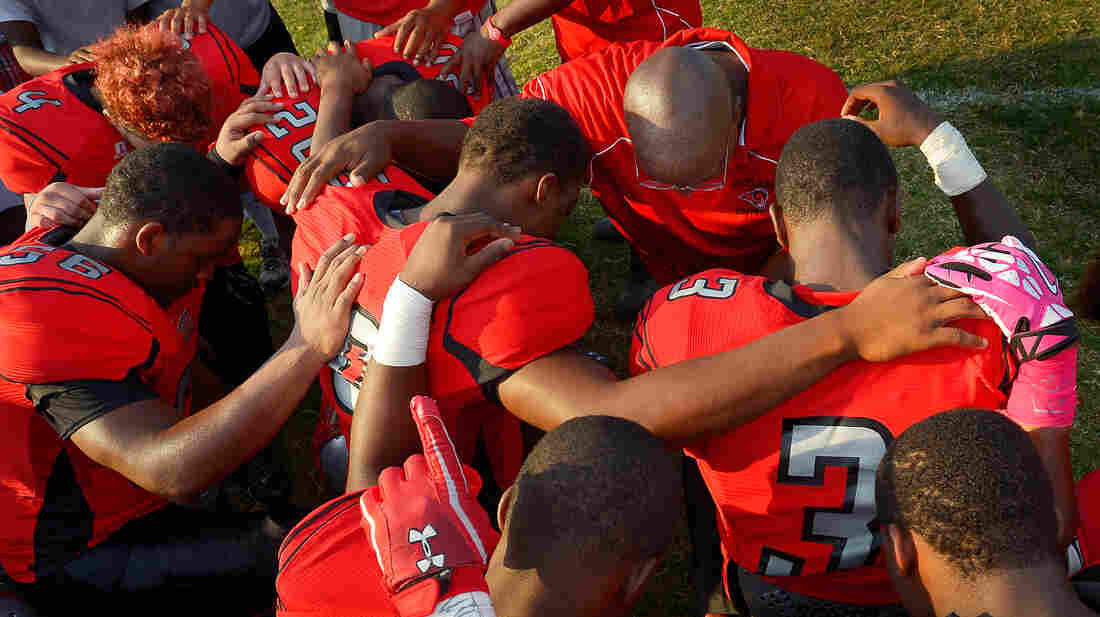 High school football players in Suitland, Md., pray with their coach Ed Shields (top right) before a game in 2013.