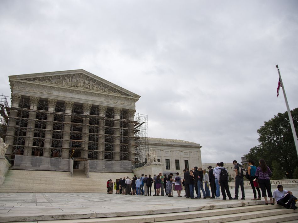 People wait in line for the beginning of the 2013-2014 Supreme Court term in Washington on Oct. 7. The court heard the first major case on campaign contribution limits since 2010's landmark <em>Citizens United</em>. (Evan Vucci/AP)