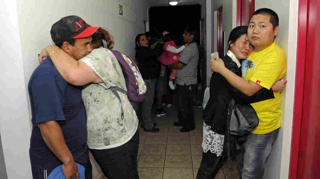 Scared residents hug in the hallway of an apartment building Tuesday after Iquique, Chile, was rocked by a strong earthquake.
