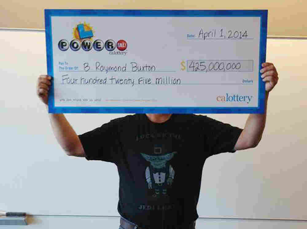 "Hidden, he is: This photo provided by the California Lottery shows Powerball winner B. Raymond Buxton holding his ceremonial check. The big winner is trying to keep his life private. He showed up in a T-shirt that says ""Luck of the Jedi, I Have."""