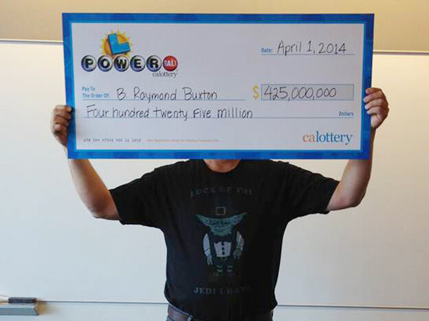 """Hidden, he is: This photo provided by the California Lottery shows Powerball winner B. Raymond Buxton holding his ceremonial check. The big winner is trying to keep his life private. He showed up in a T-shirt that says """"Luck of the Jedi, I Have."""""""