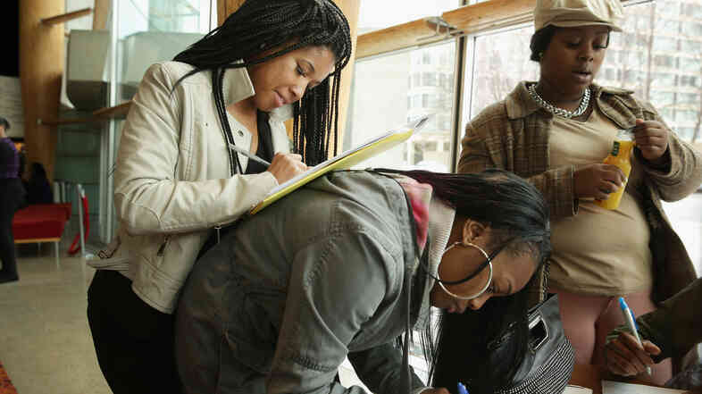 Kiara Crawford, Brittney Winkler and Jessyca Freeman (left to right) were among those applying for work last month at a job fair in Washington, D.C. Early data from that month signal that job growth may have gained some speed.