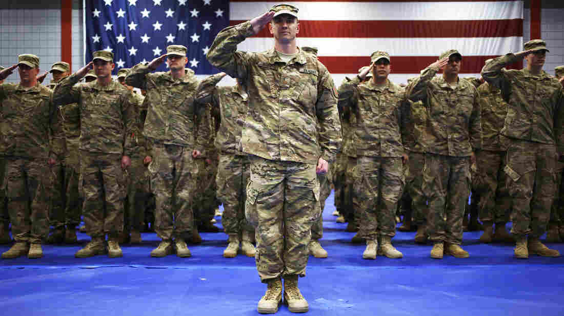 """As the U.S. winds down the Afghan war, the government is eyeing a much reduced military force — to its lowest level since World War II. Here, soldiers from the U.S. Army's 3rd Brigade Combat Team, 1st Infantry Division, salute during the playing of """"The Star-Spangled Banner"""" during a homecoming ceremony Feb. 27 in Fort Knox, Ky."""