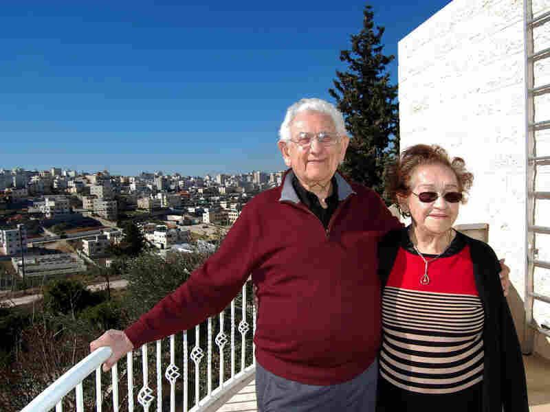 Elyakim Haetzni, who fled Hitler's Germany as a boy, stands with his wife, Tzipora, on the balcony of their home in the West Bank settlement of Kiryat Arba. Their view is of Hebron, an almost entirely Palestinian city.