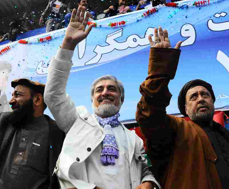 Afghan presidential candidate Abdullah Abdullah (center) and his vice presidential candidates Mohammed Mohaqiq (right) and Mohammad Khan (left) wave to their supporters at a rally in the northwestern city of Herat on Tuesday.