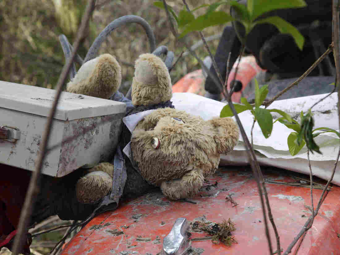 A stuffed bear sits with other items found nearby Wednesday atop a tractor that landed at the edge of the debris field in a deadly mudslide in Oso, Wash.