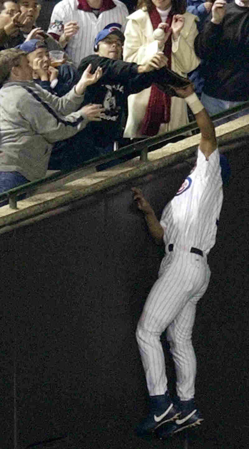 Cubs outfielder Moises Alou reaches into the stands for a foul ball during the National League Championship Series in 2003. With the Cubs leading 3-0, a fan, Steve Bartman, deflected the ball. The Florida Marlins went on to score 8 runs in the inning, winning the game and then eliminating the Cubs the next night.