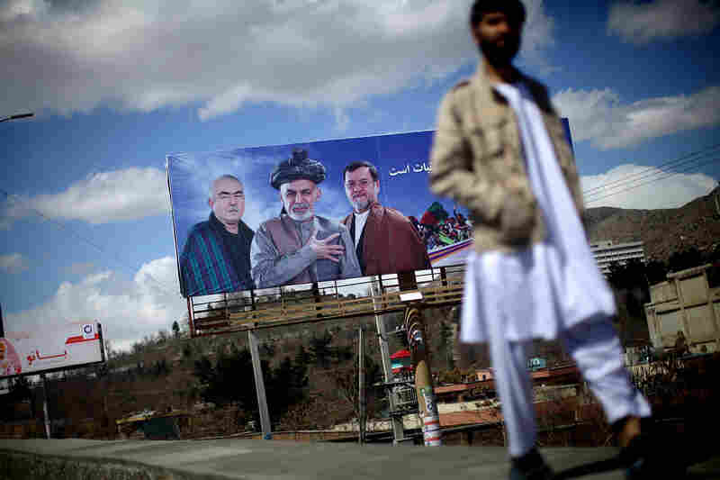 A man walks past a billboard for Ghani's campaign in Kabul.