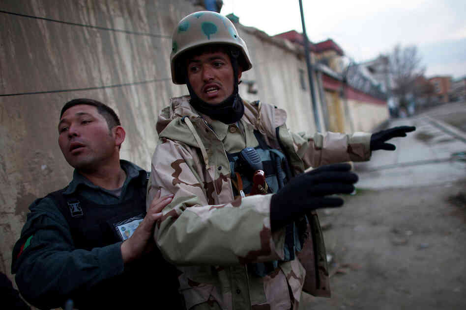 Afghan police try to control the street outside of the compound in Kabul used by the U.S.-based aid group Roots of Peace, which was rocked by gunfire and explosions on March 28.