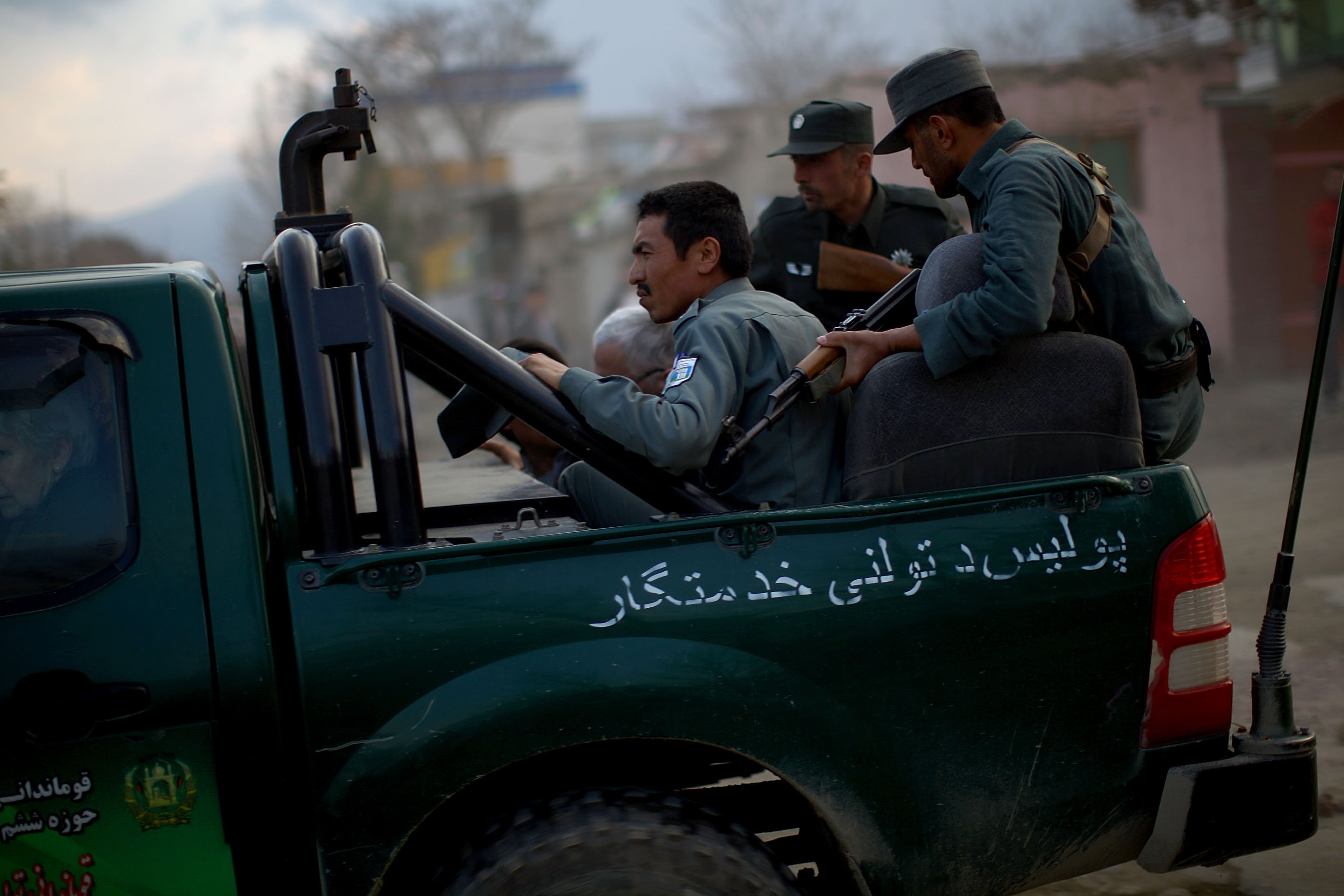 Afghan police speed away carrying foreigners from Roots of Peace. The Taliban claimed they attacked the guesthouse used by foreigners.