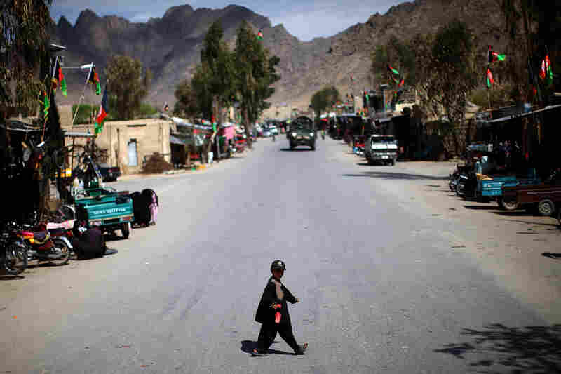 A boy walks across the street, with a U.S. Stryker behind, in the main bazaar of the Panjwai District Center. Some 90 NATO troops have been killed and more than 800 wounded in Panjwai, but today the district is considered safe. Afghan forces are now in charge of security, and they say the Taliban won't be returning to the district.