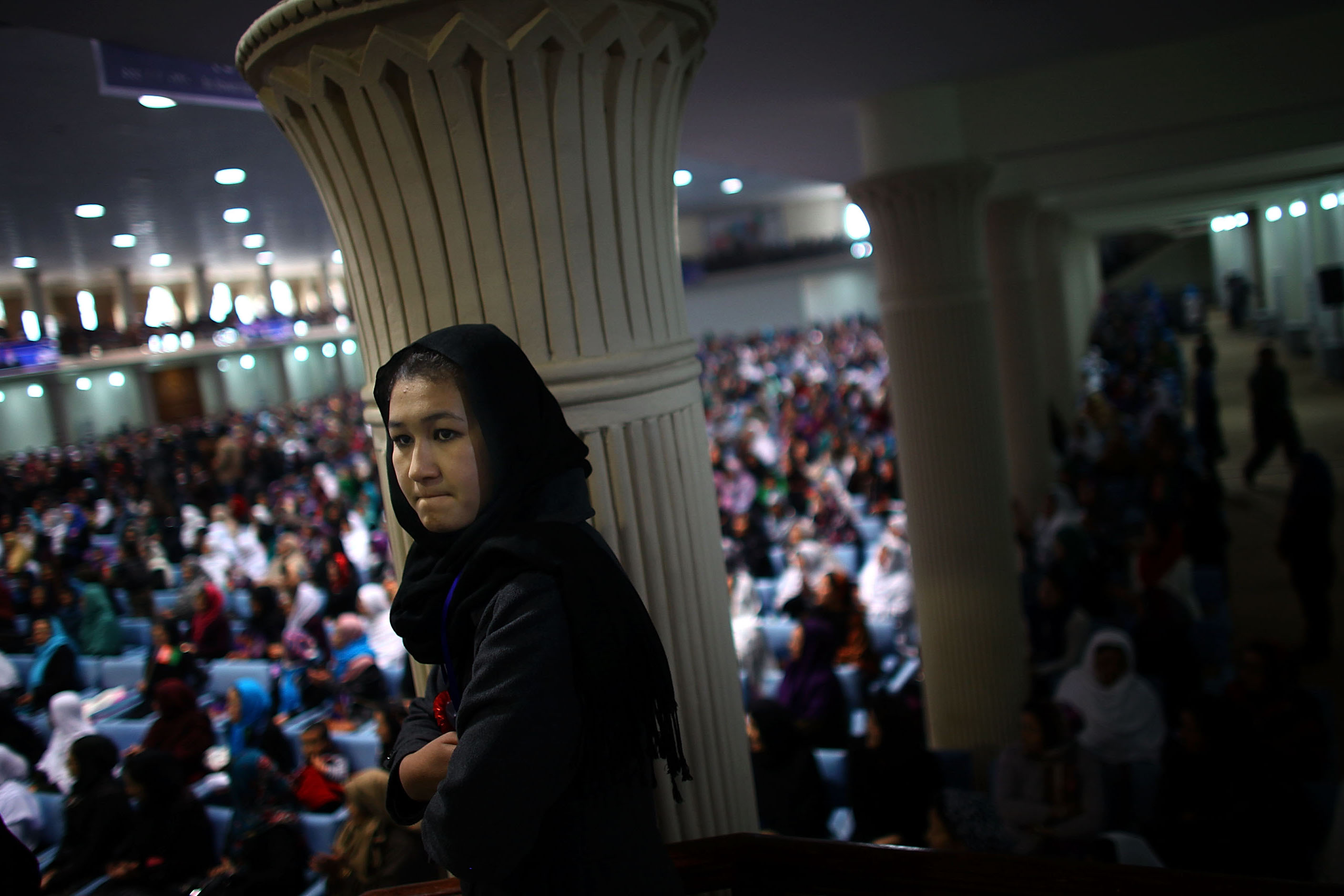 A woman stands on a stairway to get a better view of Ghani during the rally.