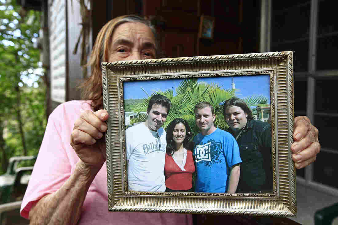 Dinora Lopez Miranda, 87, grandmother of U.S. Army soldier Iván López, holds a picture of her grandchildren, Eliezer (from left), Ivanis, Ivan and Rickey, while speaking to journalists outside her home in Guayanilla, Puerto Rico.