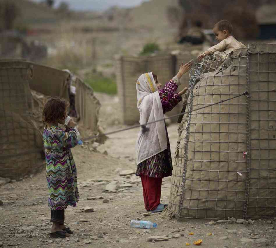 In a photo taken by Anja Niedringhaus on Thursday in Khost, an Afghan girl helps her brother down from a security barrier outside an Independent El