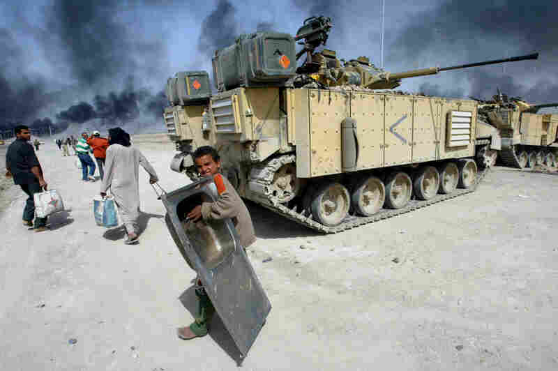 An Iraqi child carrying a sink passes by a British tank in Basra, southern Iraq, in 2003.