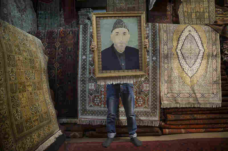 An Afghan carpet seller holds up a framed carpet depicting Afghan President Hamid Karzai in his store in Kabul on March 30.