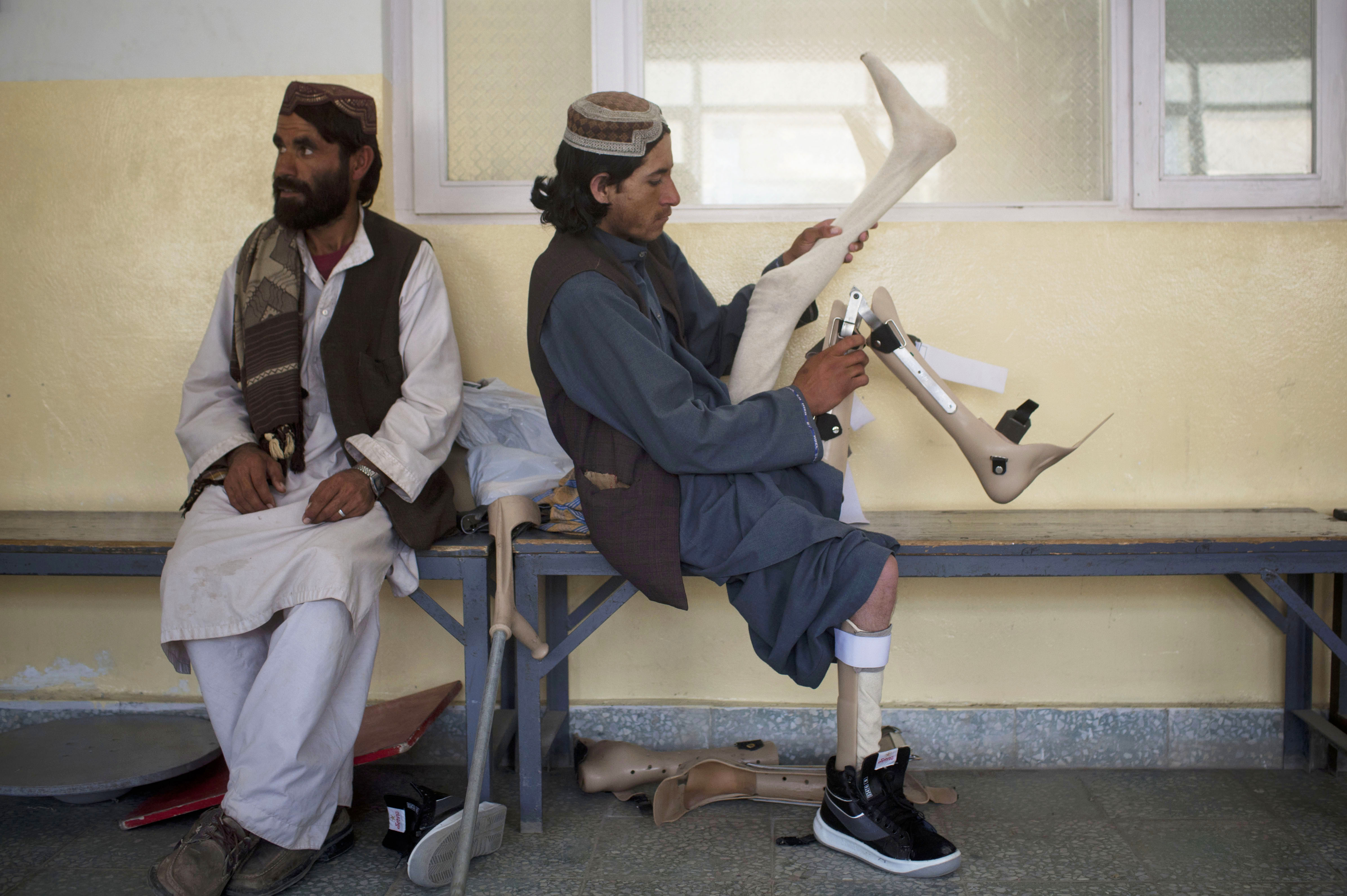 Afghan polio victim Musa, 15, is accompanied by his older brother, Nordahan, at a rehabilitation center in Kabul in 2012.