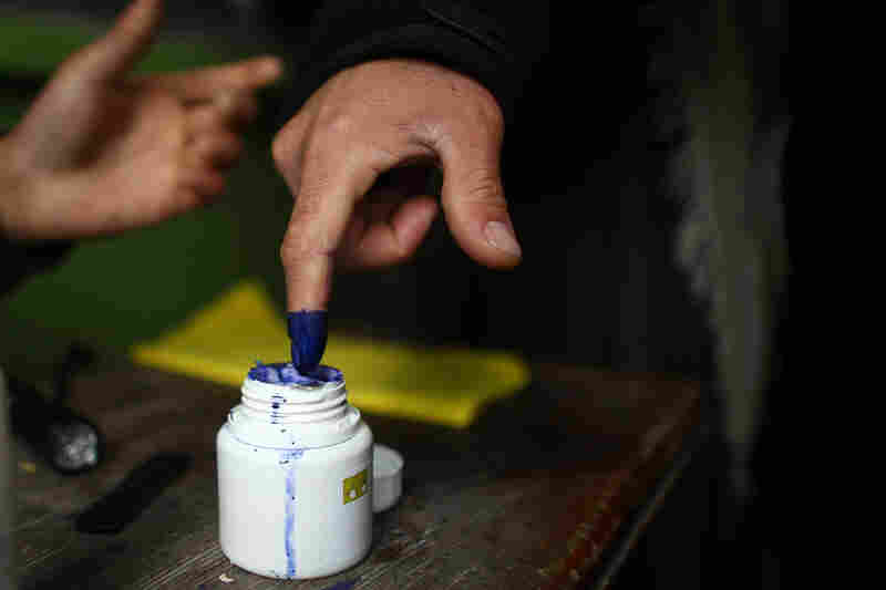 Men have their fingers inked before receiving ballots for Saturday's election.