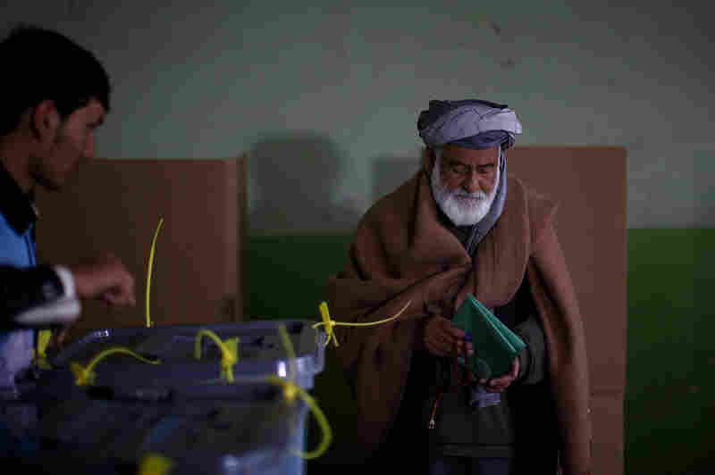 A man prepares to cast his ballot after filling out both the provincial and presidential voting forms in Kabul.
