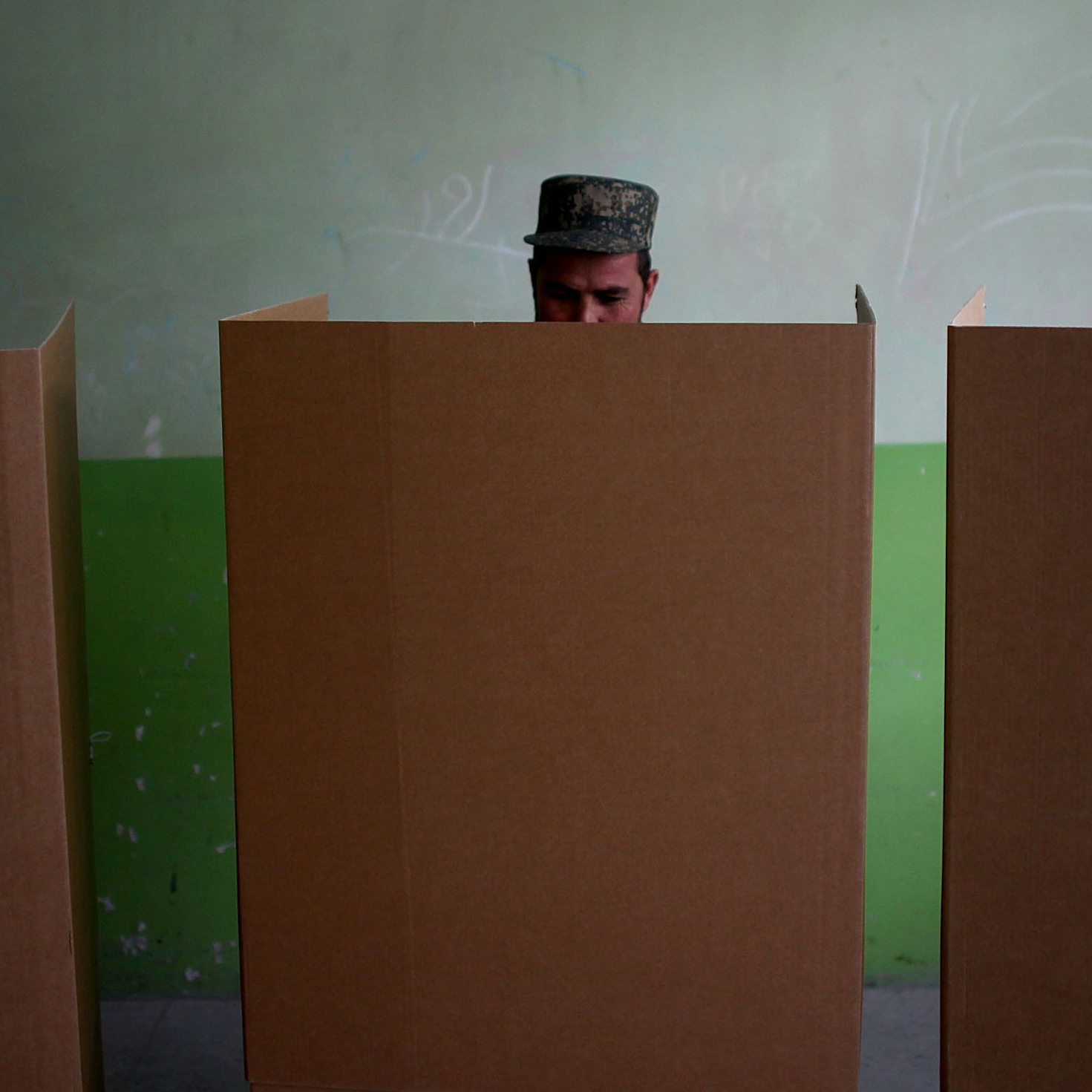 A soldier fills out his ballot behind cardboard privacy screens in a Kabul polling station.