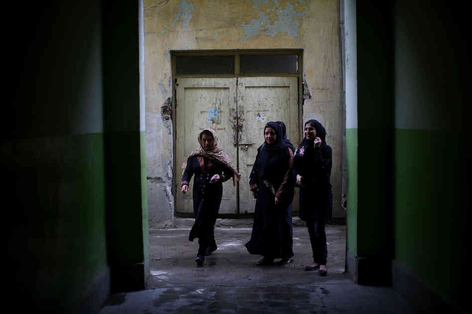 Women walk into the halls of a girls' high school in Kabul to vote.