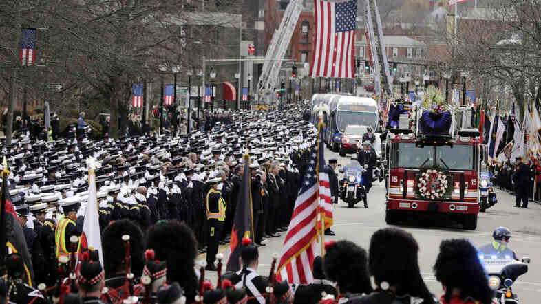 Firefighters salute the funeral procession for Lt. Ed Walsh, a Boston