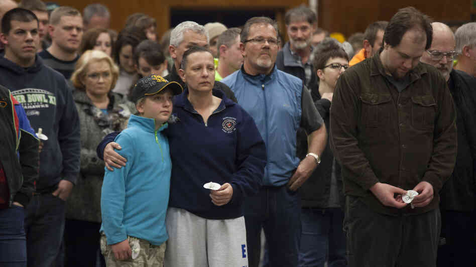 Gabriella Botamanenko (center left) hugs her mother, Angela Botamanenko, during a vigil for mudslide victims at the Darr