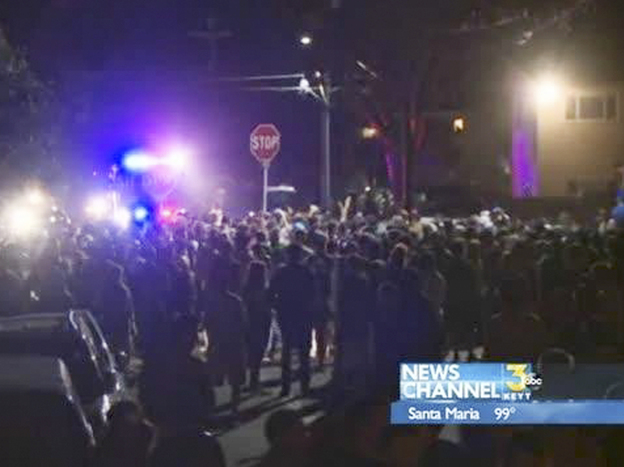 A video image from KEYT-TV shows a crowd confronting police during a weekend college party in Southern California that devolved into a street brawl. About 100 people were arrested and at least 44 people were taken to the hospital.