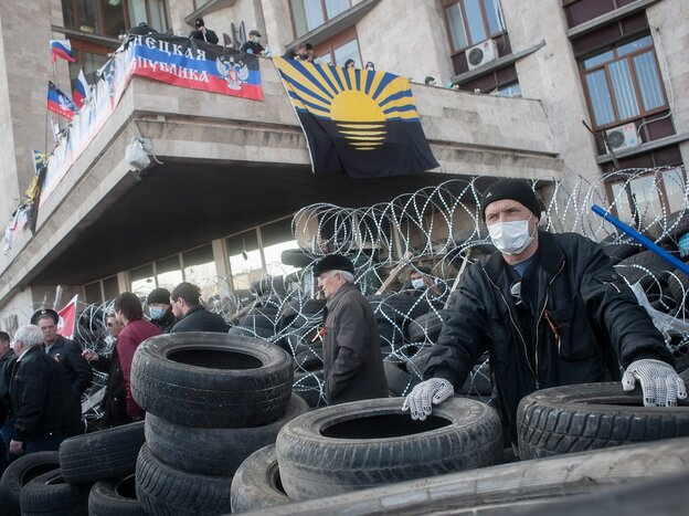 Pro-Russian protesters gather next to a barricade as they occupy the regional administration building in Donetsk, Ukraine, on Monday.