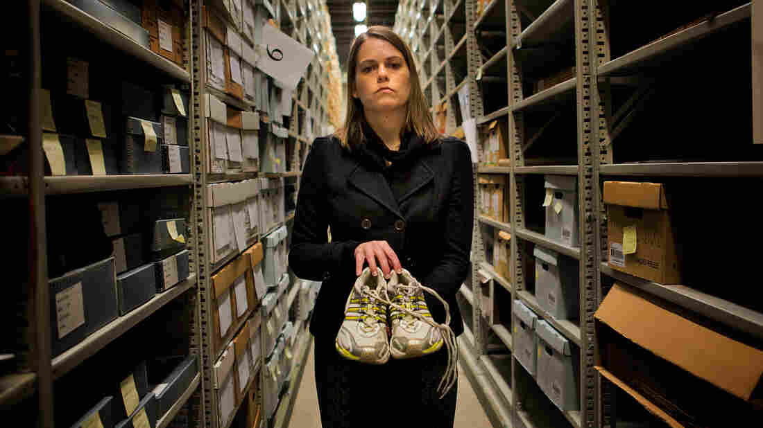 "Rainey Tisdale, curator of the ""Dear Boston"" exhibit at the Boston Public Library, holds a pair of sneakers left at the marathon bombing memorial last year."